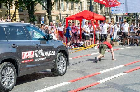 strongman: Lviv, Ukraine - July 2015: Yarych street Fest 2015. Strongman pulls Toyota Highlander