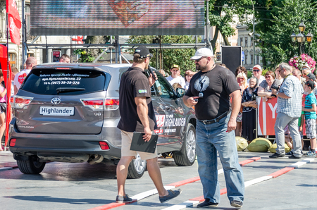 strongest: Lviv, Ukraine - July 2015: Yarych street Fest 2015. The Worlds Strongest Man Vasyl Virastuk referee consults with another judge in the background Tayota Highlander Editorial