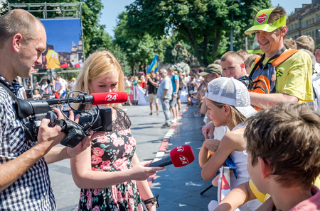 correspondent: Lviv, Ukraine - July 2015: Yarych street Fest 2015. Correspondent channel 24 interviews a girl viewer competitions strongmen Editorial