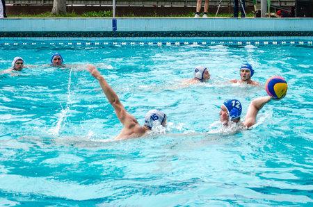 water polo: Lviv, Ucrania - Julio 2015: Ucraniano waterpolo Copa. Pelota de waterpolo del equipo Atleta en una piscina y hace atacar a tiros en encargado de la meta tratando