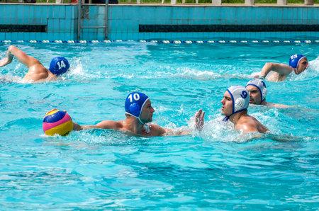 waterpolo: Lviv, Oekraïne - juli 2015: Oekraïense Cup waterpolo. Atleet team waterpolo bal in een zwembad en maakt het aanvallen schot op doel keeper proberen