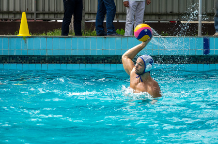 waterpolo: Lviv, Ukraine - July 2015: Ukrainian Cup water polo. Athlete teams water polo ball in a swimming pool and makes attacking shot on goal keeper trying