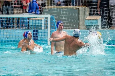 waterpolo: Lviv, Ucrania - Julio 2015: Ucraniano waterpolo Copa. Pelota de waterpolo del equipo Atleta en una piscina y hace atacar a tiros en encargado de la meta tratando