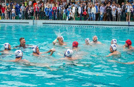 water polo: Lviv, Ucrania - Julio 2015: Ucraniano waterpolo Copa en la piscina SKA. Equipo de waterpolo celebra la victoria con el entrenador en la ropa en la piscina con champán