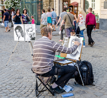 Lviv, Ukraine - July 2015: Male street artist draws a portrait of a man with a brush on the canvas in Lviv, at Market Square Editorial