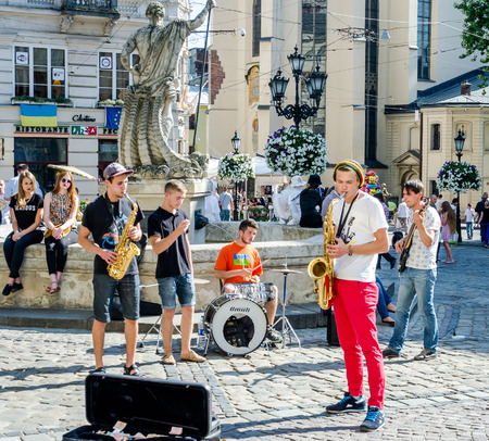 playing the market: Lviv, Ukraine - July 2015: Musicians playing the saxophone, drums and guitar giving a concert in the Market Square in Lviv before the audience