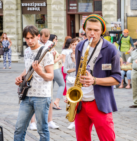 playing the market: Lviv, Ukraine - July 2015: Musicians playing the saxophone and guitar giving a concert in the Market Square in Lviv before the audience