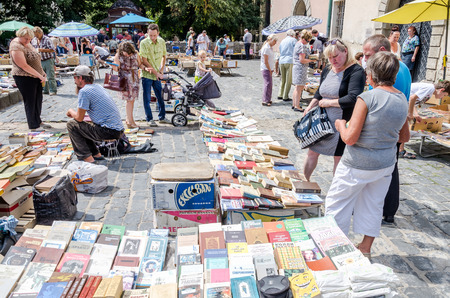 old items: Lviv, Ukraine - July 2015: Men and women choose and buy, and sellers are selling old rare books and vintage items in the book market near the monument to Fedorov in Lviv, Ukraine Editorial
