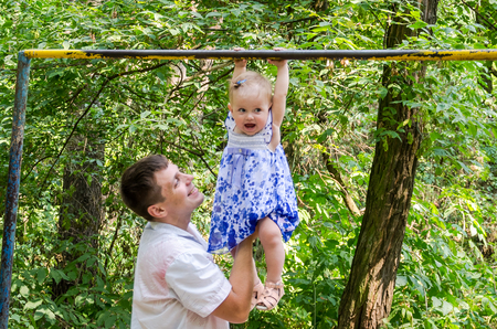 rekstok: Dad and daughter playing in the park on a background of trees, baby girl hanging on the horizontal bar and the father of her support