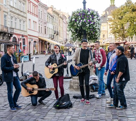 playing the market: Lviv, Ukraine - September 2015: Band of guys playing guitars and singing in the Market Square in the street in Lviv