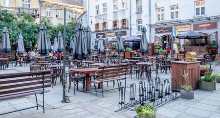 lvov: Lviv, Ukraine - September 2015: Street cafe with empty tables and chairs with umbrellas with colorful lights in the historic city of Lvov