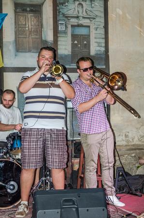 lviv: Lviv, Ukraine - September 2015: Musicians playing trumpet in Lviv cafes before the audience fans Editorial