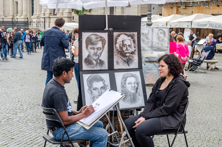 Roma, Italy - October 2015: A talented street artist draws a pencil on paper portrait of a woman sitting on a chair near the fountains of Piazza Navona in Rome, capital of Italy