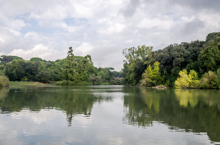 path to wealth: Lake in the park among the trees and bushes in cloudy weather at Vila Pampilii in Rome, capital of Italy