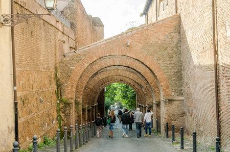 arcos de piedra: ROMA, ITALIA - OCTUBRE 2015: Los turistas que dan un paseo por las antiguas calles históricas de Roma, bajo los arcos de piedra en la zona en la iglesia de San Juan y San Pablo Editorial
