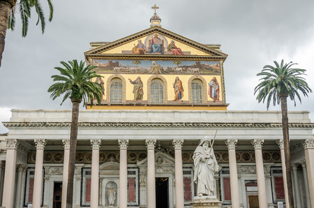 purgatory: Golden dome with a roof and a courtyard with palm trees and a statue of the cathedral church of the Basilica of St. Paul Fuori le Mura with the image of Jesus Christ and the Holy Apostles in Rome Stock Photo