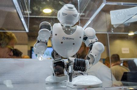 Drone robot de metal de plástico Ubtech blanco con cámaras de video para los ojos que se sientan en el podio
