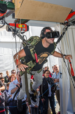 ROMA, ITALY - OCTOBER, 2015: Man experimenter feels the installation simulator skydiving glasses with virtual reality and flight simulation computer program hanging on the ropes on the winches managed Editoriali