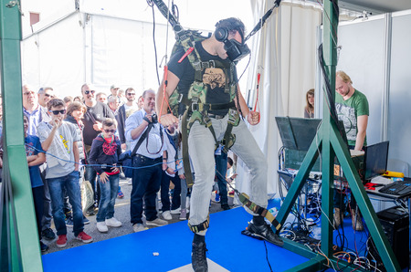 experimenter: ROMA, ITALY - OCTOBER, 2015: Man experimenter feels the installation simulator skydiving glasses with virtual reality and flight simulation computer program hanging on the ropes on the winches managed Editorial
