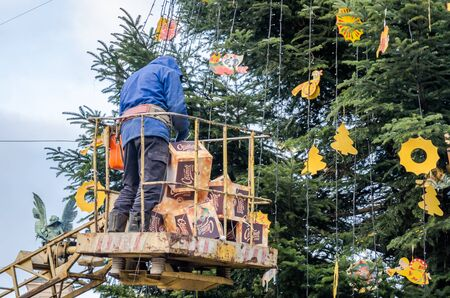 party poppers: LVIV, UKRAINE - DECEMBER, 2015: Working men in a basket at the height of the machine tap dress up toys and decorations Christmas tree on Liberty Avenue in front of the Opera House in Lviv Editorial