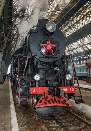 peron: LVIV, UKRAINE - DECEMBER, 2015: Old Soviet vintage black retro train with a red star at the railway station in Lviv produces steam from the pipes and the passengers waiting on the landing Peron Editorial