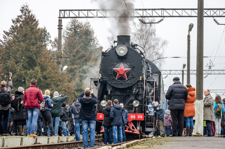 reserved seat: LVIV, UKRAINE - DECEMBER, 2015: Old vintage retro black locomotive with red star arrived at the station where he was photographed passengers and tourists Editorial