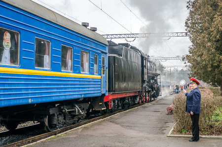 peron: LVIV, UKRAINE - DECEMBER, 2015: Old vintage retro black locomotive with red star arrived at the station where he was photographed passengers and tourists Editorial