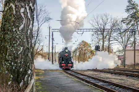 reserved seat: LVIV, UKRAINE - DECEMBER, 2015: Old iron black retro vintage Soviet steam locomotive with red star arrives at the railway station to board passengers in the clouds of steam