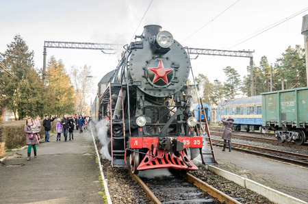 peron: LVIV, UKRAINE - DECEMBER, 2015: Old iron black retro vintage Soviet steam locomotive with red star arrives at the railway station to board passengers in the clouds of steam