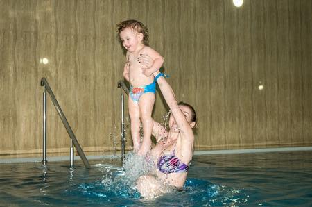 sauna nackt: Junge sch�ne Mutter und ihre Tochter, gl�ckliche Familie, spielen, herumalbern und Schwimmen in einem Pool von blauem Wasser, mit positiven Emotionen l�chelnd und Spa�, sind sie Fliegenspray Lizenzfreie Bilder