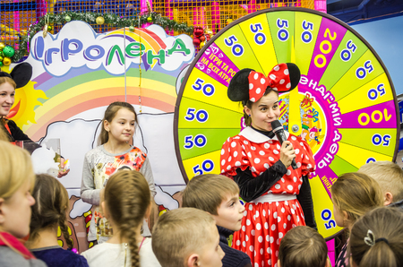 actress girl: LVIV, UKRAINE - JANUARY 2016: Leading actress girl dressed as a mouse in a red dress with white polka dots is a childrens holiday near the wheel of fortune with numbers lottery surrounded by children Editorial
