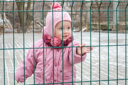 locked in: Little beautiful girl baby behind the fence, grid locked in a cap and a jacket with sad emotion on his face