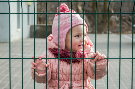 shut down: Little beautiful girl baby crying with tears in his eyes and a sad, sad emotions shut down as a punishment for a fence of metal lattice want freedom, wearing a hat and down jacket Stock Photo