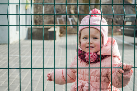 Little beautiful girl baby crying with tears in his eyes and a sad, sad emotions shut down as a punishment for a fence of metal lattice want freedom, wearing a hat and down jacket Stock Photo