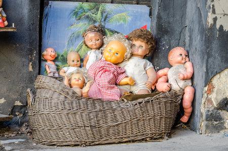 Colección de los niños abandonados viejos de peluche y juguetes de plástico retro vendimia y muñecos de pie en un viejo mueble de madera en el patio en la calle