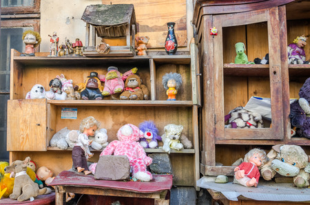ni�os abandonados: Collection of children abandoned old vintage retro plush and plastic toys and dolls standing on an old wooden furniture in the yard on the street