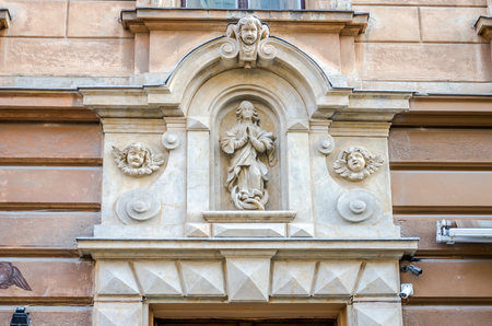 double glazing: Religious statue of holy woman who prays with her hands folded, surrounded by heads of angels who look at it, on the facade of one of the historic buildings on the street of Lviv, Ukraine Stock Photo