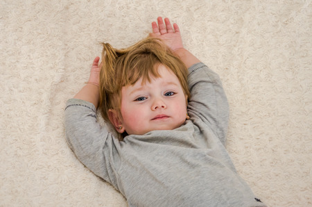 pierced ears: Little charming girl child, baby with pierced ears pierced on the bed in the morning when waking up and stretching raises his hands up