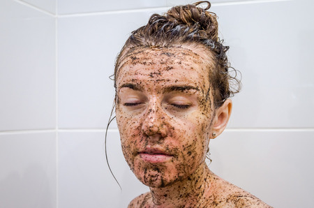 Face of a young beautiful girl on black coffee is deposited mask, taking a bath on the background of white tiles