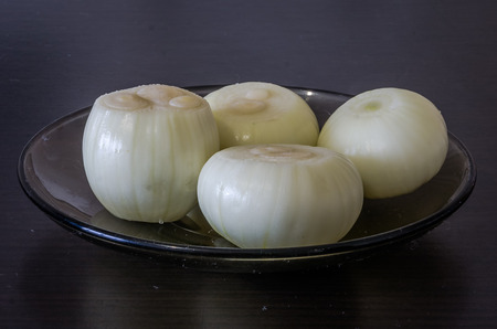 purified: Glass plate on black table with purified onion prepare for cooking