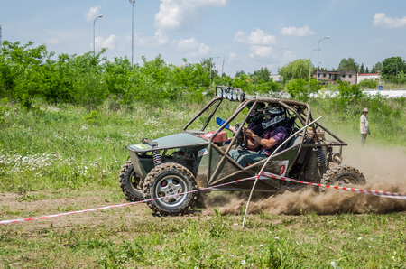 spectators: LVIV, UKRAINE - MAY 2016: Homemade machine built with tuning rally buggy rides with the driver and co-driver at high speed past the spectators along the dusty road