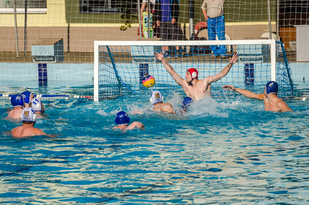 attacker: LVIV, UKRAINE - JUNE 2016: Athletes water polo players fighting for the ball with the opponents in the pool of water in a spray