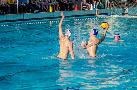 opponents: LVIV, UKRAINE - JUNE 2016: Athletes water polo players fighting for the ball with the opponents in the pool of water in a spray