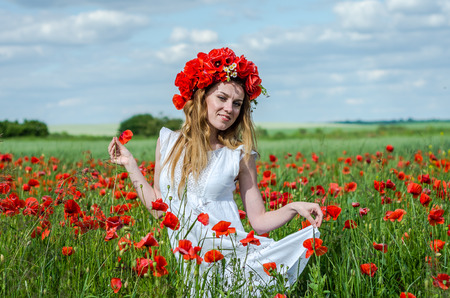 Young beautiful happy girl with long hair in a white dress in the poppy field with a wreath on his head