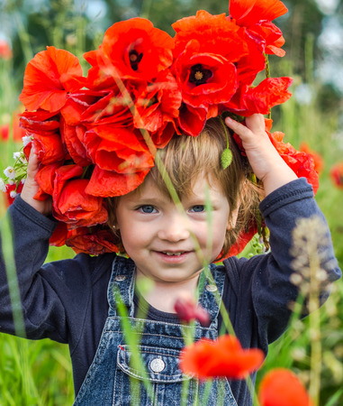 Little girl baby playing happy on the poppy field with a wreath, a bouquet of color A red poppies and white daisies, wearing a denim dress blue, charming, joyful child with a smile on his face Stock Photo