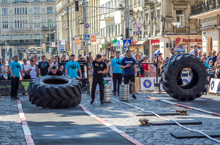 sports form: LVIV, UKRAINE - JUNE 2016: A strong man in the sports form bodybuilder raises heavy wheel on the street