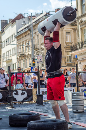 sports form: LVIV, UKRAINE - JUNE 2016: A strong man in the sports form bodybuilder lifts a heavy barbell on the street