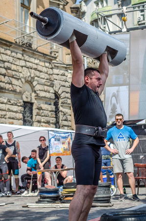 profesional: LVIV, UKRAINE - JUNE 2016: A strong man in the sports form bodybuilder lifts a heavy barbell on the street