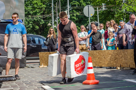 profesional: LVIV, UKRAINE - JUNE 2016: Strongman with a large inflated metal body carries heavy suitcases