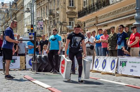strongman: LVIV, UKRAINE - JUNE 2016: Strongman with a large inflated metal body carries heavy suitcases
